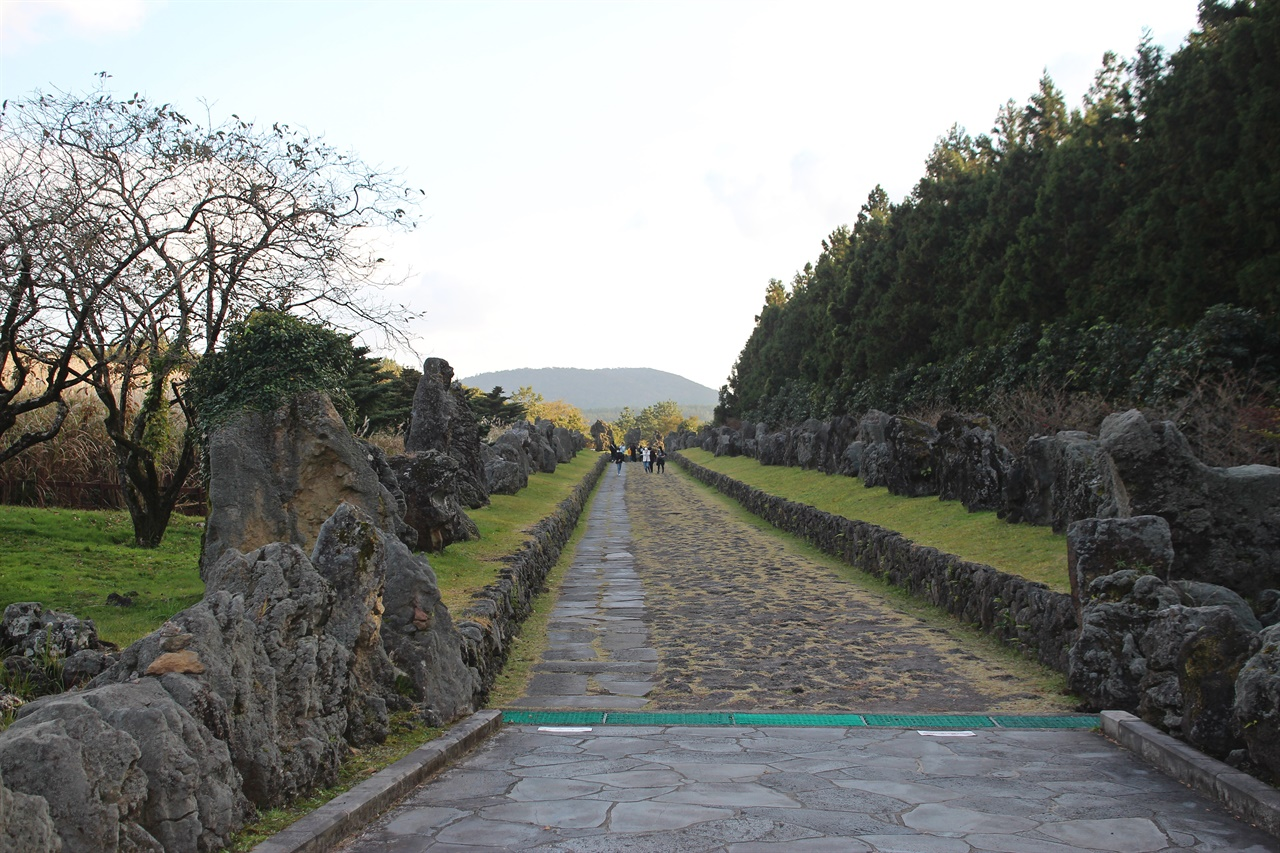 산굼부리 입구에 기암괴석이 전시된 산책로 모습