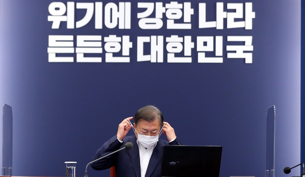 문재인 대통령이 26일 청와대에서 열린 수석·보좌관 회의에서 발언에 앞서 마스크를 벗고 있다.