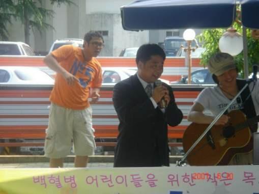 백혈병 어린이를 위한 모금 공연 뒤로 육중완 씨가 무언가에 열중하고 있다.