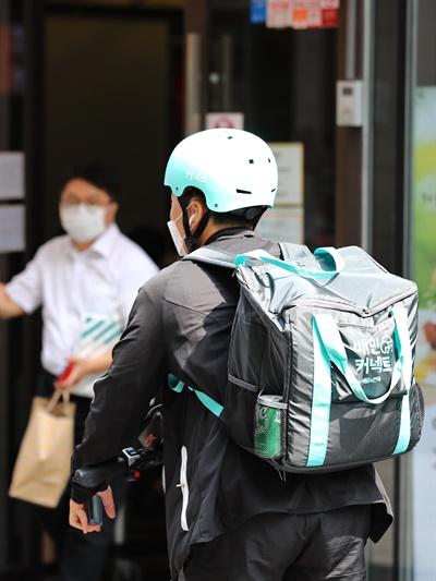 10일 점심시간 서울 시내에서 배달하는 라이더 뒤로 햄버거를 포장한 시민이 가게를 나서고 있다. 2020.9.10
