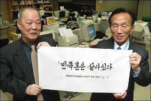오마이뉴스 편집실에서 권중희 선생(오른쪽)과 기자. 글씨는 권중희 선생의 작품이다.
