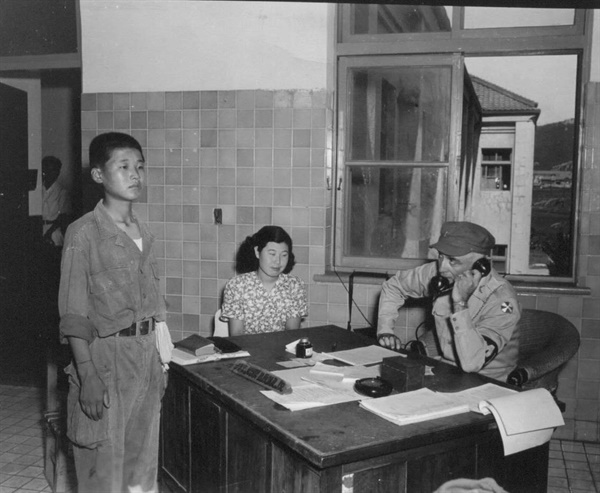 한국전쟁 당시 미8군 하사관이 가장 나이 어린 소년 인민군 포로를 신문하는 장면(가운데는 통역).