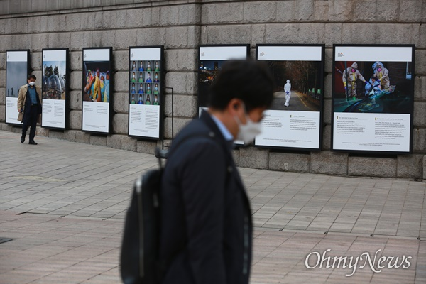 18일 서울도서관(옛 서울시청)앞에서 진행중인 '2020 서울 글로벌 포토저널리즘 사진전 : 2020 서울, 다시 품은 희망'에 코로나19로 고통받거나 극복하기 위해 노력하는 전세계인의 모습이 담긴 가운데 마스크를 쓴 시민들이 지나고 있다. 서울시는 최근 코로나19 확진자 급증에 따라 다음날인 19일 0시부터 2주간 사회적 거리두기가 1.5단계로 격상되고 방역초치가 강화될 예정이다.