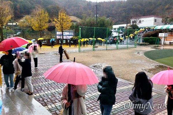 비가 내리는 속에 11월 19일 창원진해 한 학교에 마련된 선별진료소에서 많은 사람들이 코로나19 진단검사를 받고 있다.