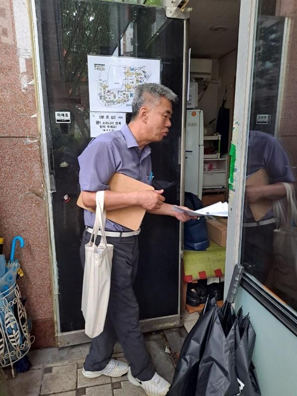 용산구의 아파트 경비노동자를 만나 유인물을 나눠주며 노동자지원센터 설립의 중요성을 이야기하고 있다.