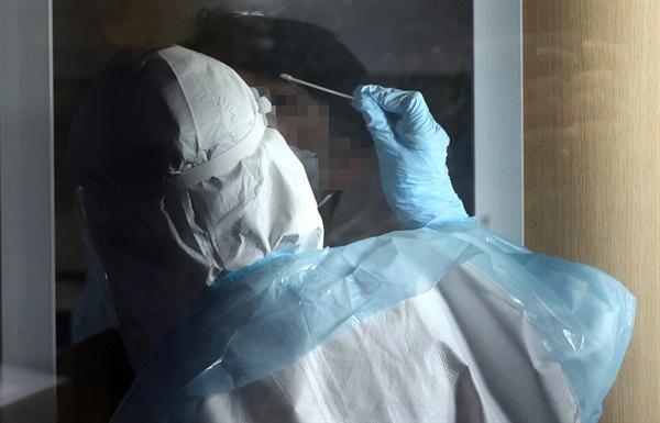 신종 코로나바이러스 감염증(코로나19) 국내 신규 확진자 수가 230명을 기록한 17일 오후 서울 성동구보건소에 마련된 선별진료소에서 의료진이 검체를 채취하고 있다
