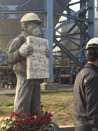 조각상이 되어 발전소현장에 서있는 김용균 김용균 1주기 태안화력발전소 현장추모제