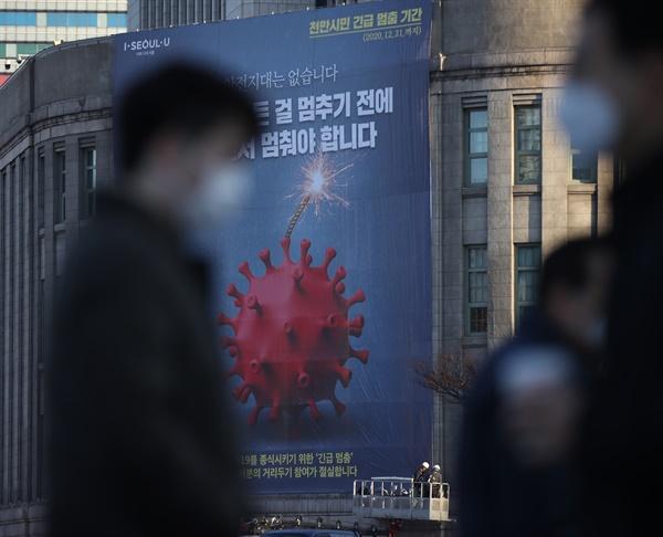 25일 오전 서울도서관 외벽에 천만 시민 긴급 멈춤 기간을 알리는 대형 현수막이 설치되고 있다.