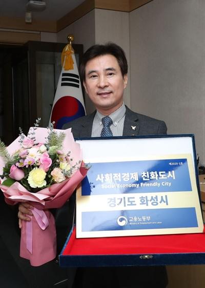 서철모 화성시장이 26일 고용노동부로부터 '사회적경제 친화도시' 선정패를 받고 기뻐하고 있다.