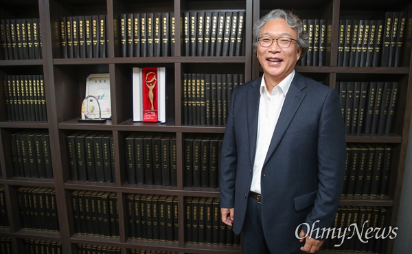 박승흡 <매일노동뉴스> 회장이 1993년 창간 때부터 최근까지 발행한 신문을 정리해 놓은 합본 앞에서 포즈를 취하고 있다.