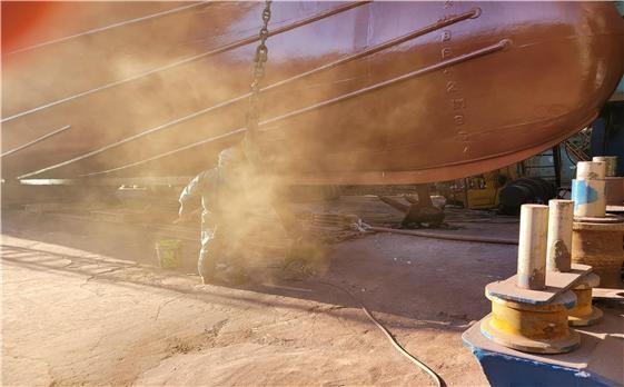 야외연마 작업으로 먼지가 흩날리는 장면.