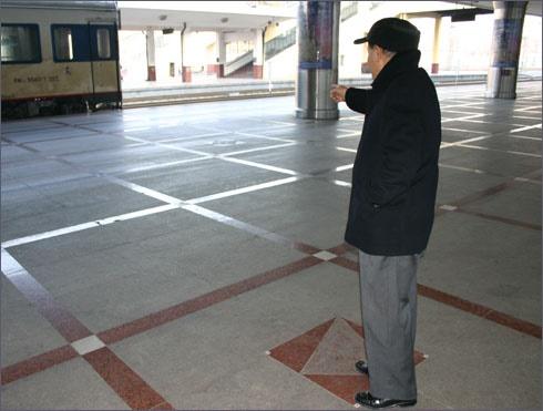 안중근 의사의 의거지 표지(세모꼴)에서 김우중 선생이 이토히로부미가 쓰러진 자리(마름모꼴)를 권총 사격자세로 가리키고 있다(2009. 10. 31. 촬영).