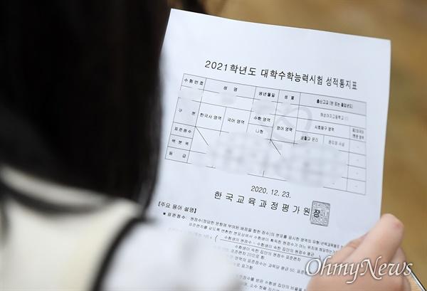 2021학년도 대학수학능력시험(수능) 성적통지표 배부일인 23일 오전 서울 동대문구 해성여자고등학교에서 학생들이 수능 성적표를 확인하고 있다.