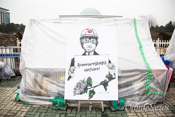 29일 오전 서울 국회 앞에서 중대재해기업처벌법 재정 촉구 농성장 뒤로 국회의 지붕이 보이고 있다.