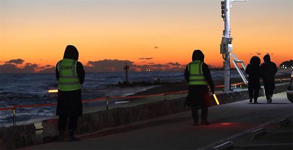 2021년 1월 1일, 매서운 날씨 속에서도 강릉 경포 해변에 배치된 해맞이 단속요원들이 일출 관광객들을 단속 활동을 하고 있다.
