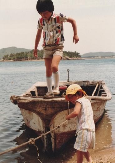 다정한 형제 바닷가에서 조그만 배 위에 올라 끙끙거리는 형과 아우.