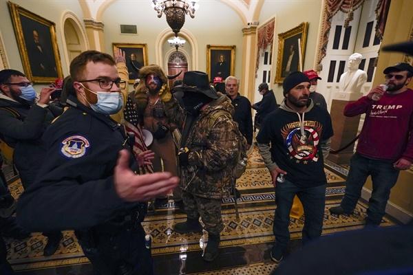 미 연방 의회 의사당에 진입한 시위대와 이를 감시하는 경찰관 미 연방 의회 의사당에 진입한 시위대와 이를 감시하는 경찰관