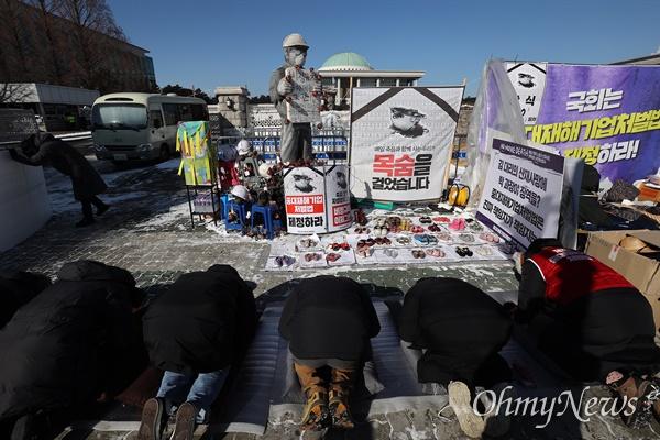 7일 오후 서울 여의도 국회앞에 설치된 중대재해기업처벌법 제정 촉구 농성장에서 노동자들이 108배를 하고 있다.