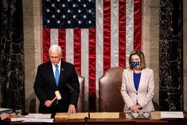 6일(미국 현지시각) 마이크 펜스 미국 부통령(사진 왼쪽)과 낸시 펠로시 하원의장(오른쪽)이 워싱턴D.C. 공동의회 회의에서 2020년 미국 대선 선거인단 투표 결과를 인증하고 있는 모습. 이로써 바이든 당선인의 승리가 공식 확정됐다.