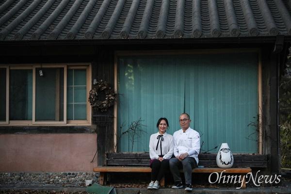 <작은 가게에서 진심을 배우다>의 저자인 김윤정 '고기리막국수' 대표와 남편 유수창 대표가 옛 고기리막국수 가게 앞에서 기념촬영을 하고 있다.