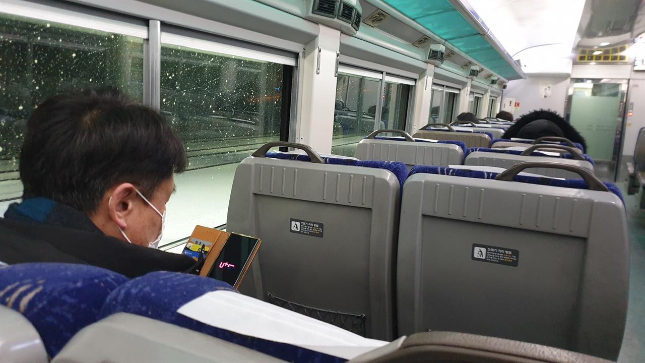 열차의 객실 내부. 승객들이 휴대전화를 검색하거나 잠을 자고 있다.