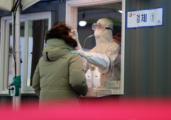 12일 오전 서울역 광장에 마련된 코로나19 임시 선별검사소에서 의료진이 검체채취를 하고 있다.
