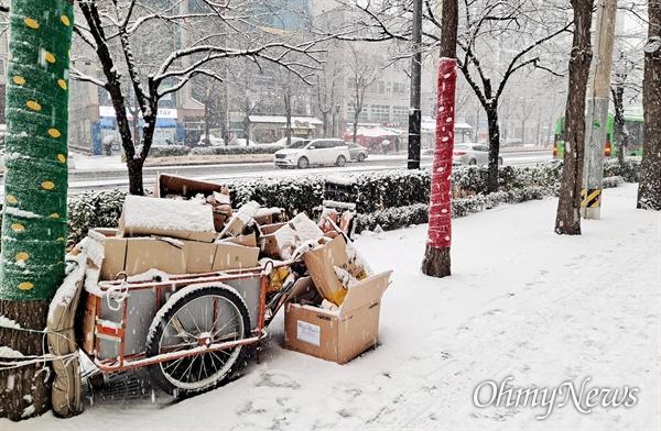 지난 12일 오후, 눈이 내린 서울 시내의 모습. 거리 한편에 놓인 재활용품 수집 리어카에도 하얗게 눈이 쌓였다.