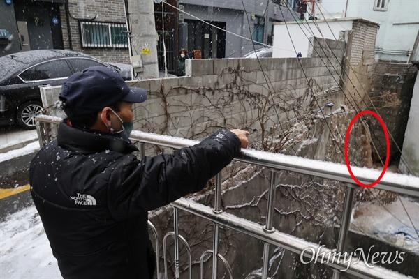 """12일 오후 서울 용산구 동자동 쪽방촌에서 거주하는 고주근(가명·70대)씨가 공동으로 사용하는 화장실 정화조에 오물(붉은색 표시)이 벽을 타고 흘러나와서 """"못 살겠다""""고 토로했다."""