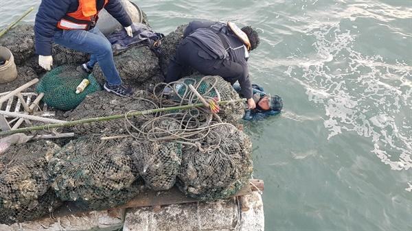 바다에 빠진 안모씨가 한손으로 뗏마를 붙잡고 버티고 있는 가운데 태안해경 직원들이 구조 작업을 펼치고 있다.