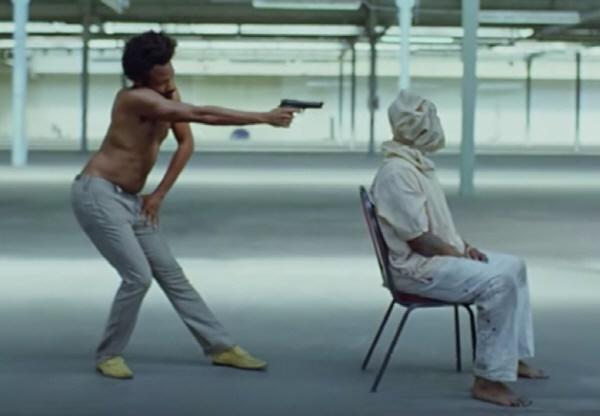 'This Is America'의 뮤직비디오 초반부 한 장면. 부자연스러운 차일디시 감비노의 동작에 대해 19세기 인종 차별의 상징적인 캐릭터 짐 크로(Jim Crow)를 은유했다는 주장이 있다.