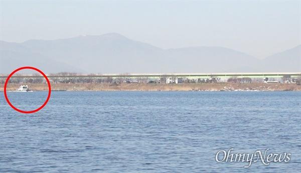 낙동강 하구의 고니 떼를 향해 달리는 부산시 낙동강관리본부 청소선.