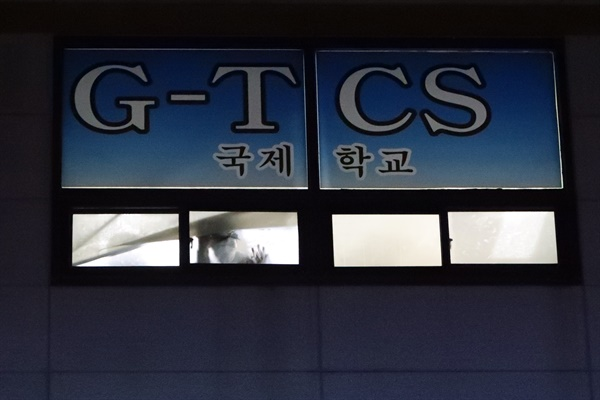26일 오후 광주 광산구 운남동 광주TCS국제학교에서 한 합숙생이 창밖을 내다보고 있다. 방역 당국은 학생 122명이 합숙한 이곳에서 100명이 코로나19에 확진됐다고 밝혔다.