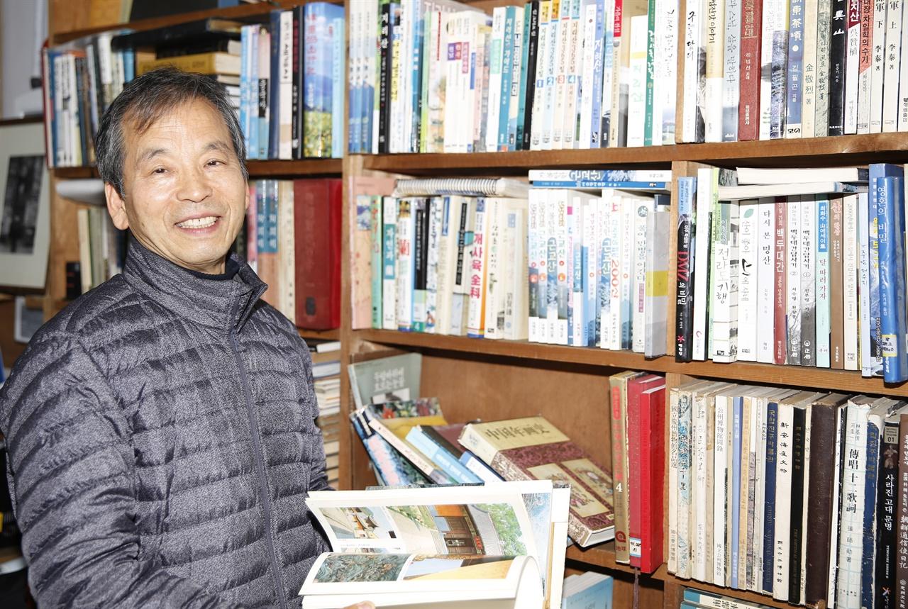 섬진강책사랑방의 김종훈 책방지기가 책을 펴들고 활짝 웃고 있다.