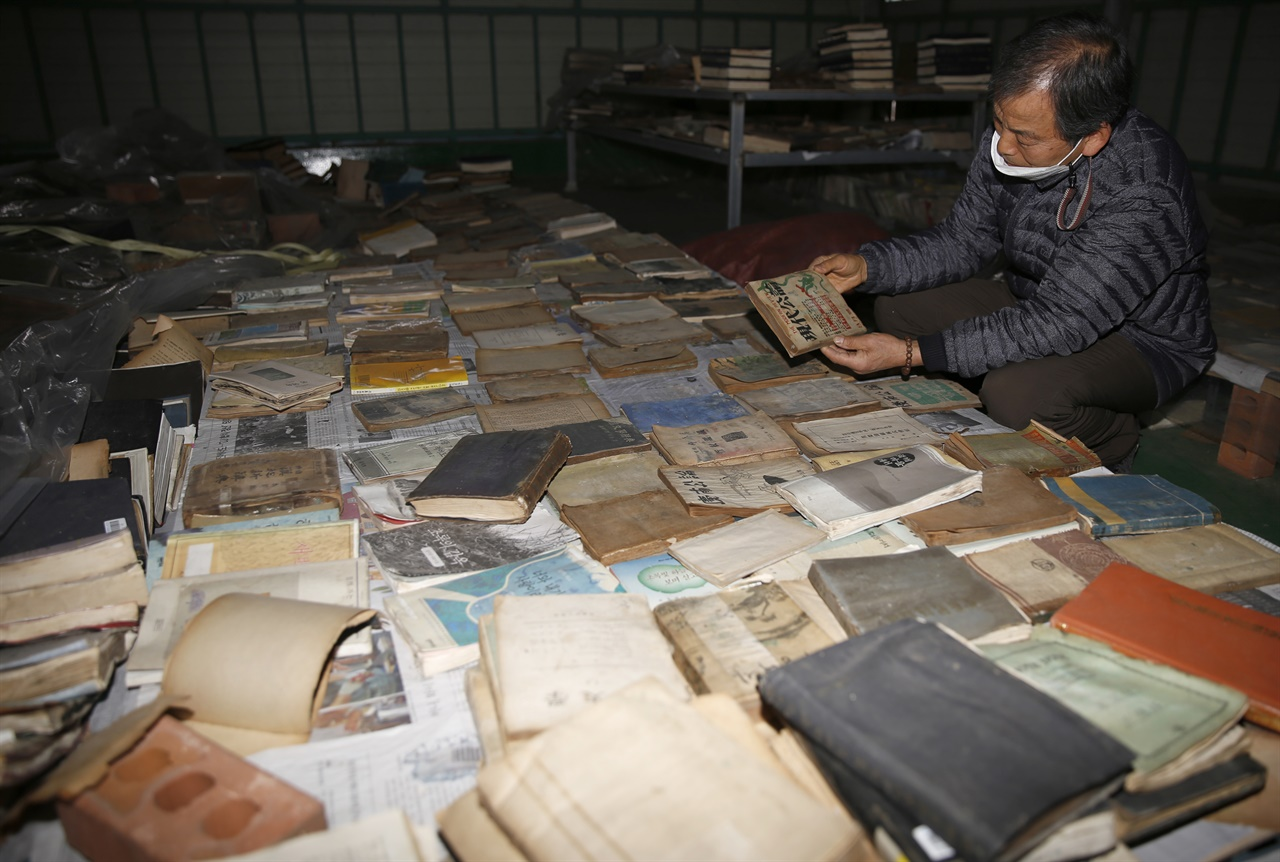 김종훈 책방지기가 지난 여름 수해를 입은 책을 살피고 있다. 책은 책방의 옥상에 따로 펼쳐져 있다.