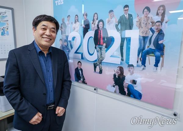 이강택 TBS 대표이사가 16일 오후 서울 마포구 TBS 사옥 자신의 집무실에 걸려 있는 TBS 프로그램 진행자들의 사진 앞에서 포즈를 취하고 있다.