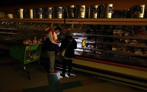 달라스에 위치한 식료품 점에서 고객들이 휴대폰 불빛을 이용하여 식품을 확인하고 있다.
