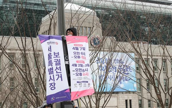 지난 16일 서울 중구 서울시청 앞 광장에서 서울시 선거관리위원회 관계자들이 선거를 홍보하는 현수막을 게시하고 있는 모습.