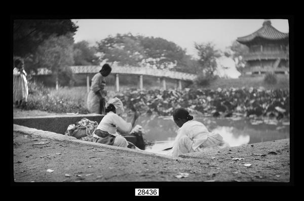 경복궁 향원정 연못에서 빨래하는 아낙네들. 1906년 무렵. 사진 국립민속박물관. 책 128쪽에서/ 경복궁 향원정의 열상진원 샘에서 빨래하는 아낙들의 모습을 찍은 흑백 원판 필름. 1906~7년 한국 등을 방문한 독일 장교 헤르만 산더(1868~1945)가 일본인 사진작가 나가노를 고용하여 촬영한 필름 자료임(국립민속박물관 해당 사진 설명)