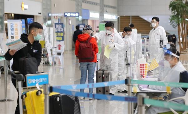 코로나19 신규 확진자 수가 이틀 연속 400명대를 기록한 4일 오전 인천국제공항 제2여객터미널에서 해외입국자들가 방역 관계자의 안내를 받고 있다.