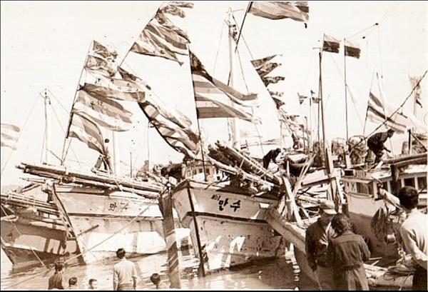 오색기 나부끼며 째보선창에 정박한 고깃배들(1960년대)