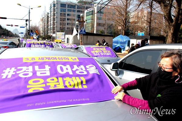 김윤자 경남여성단체연합 대표가 8일 오전 경남도청 앞에서 차량에 '세계여성의날' 관련 손펼침막을 부착하고 있다.