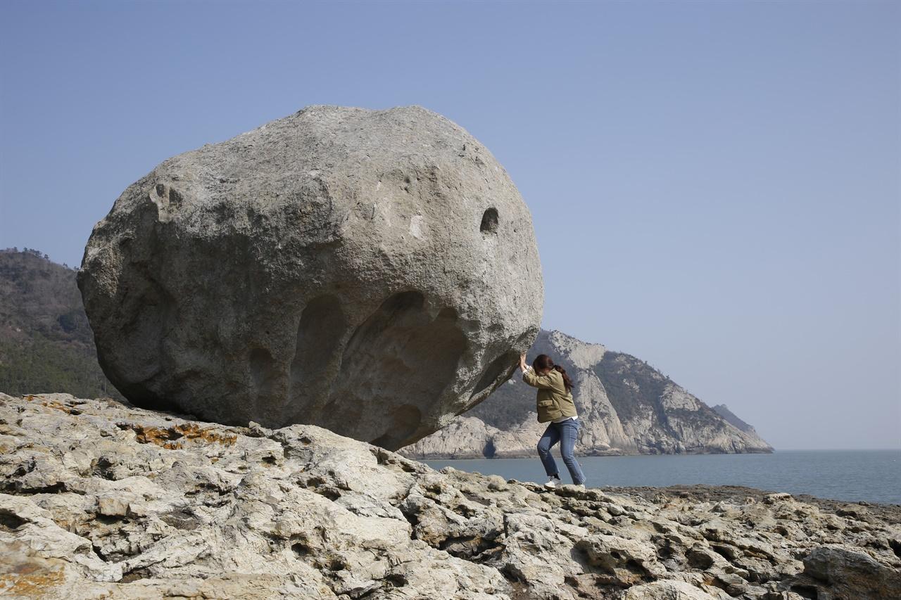 진도 관매도의 꽁돌. 설악산의 흔들바위만 하다. 한 여행객이 꽁돌을 굴리는 흉내를 내보고 있다.