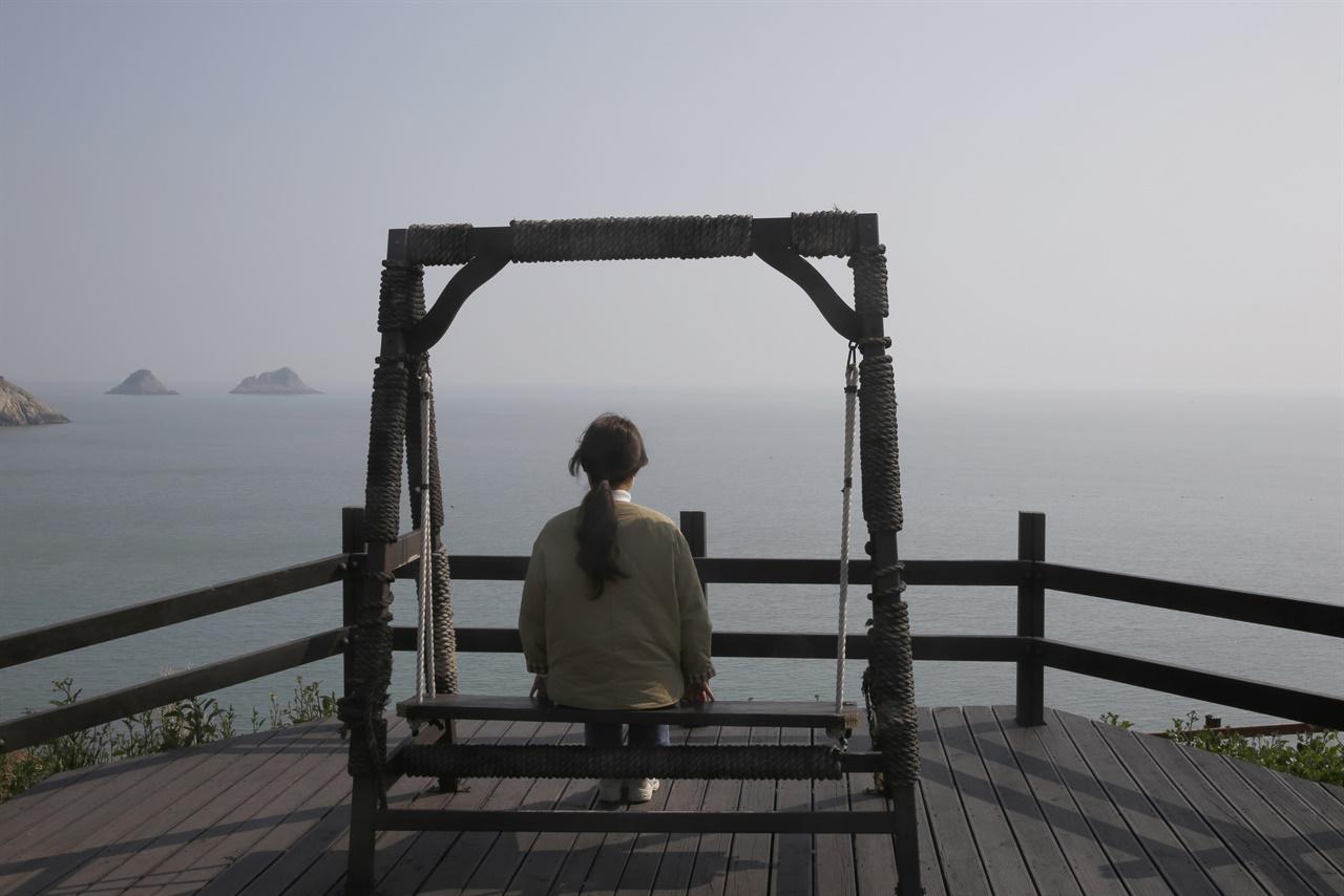 바다를 바라보는 관매도의 흔들의자.한 여행객이 의자에 앉아 바다를 바라보고 있다. 관호마을 뒤편 언덕에 설치돼 있다.
