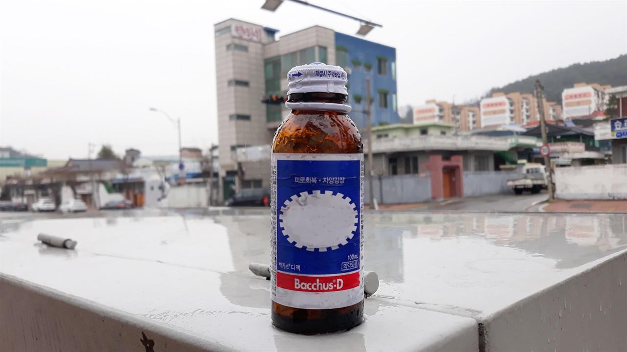 비 오는 날, 지상변압기 위에 누군가 마시고 버린 빈 '박OO'병이 올라앉아 있었다.