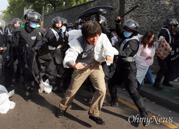 1일 오전 7시 45분경 서울 안국동 네거리에서 강제해산작전에 나선 경찰이 도망치는 한 시민을 몽둥이로 때리고 있다.