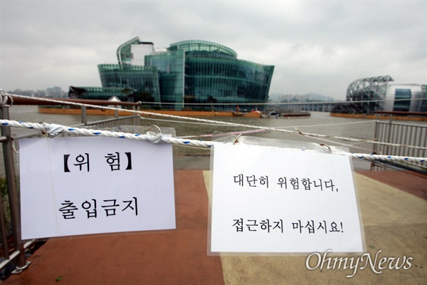 """27일 오전 장마와 태풍으로 한강물이 불어난 가운데 서울 반포대교 부근 세빛둥둥섬 입구에 '대단히 위험합니다. 접근하지 마십시요!"""" """"위험 출입금지"""" 안내문이 붙어 있다. 세빛둥둥섬으로 시민들이 들어가는 다리와 3개의 인공섬을 연결하는 다리는 모두 철거된 상태이다."""