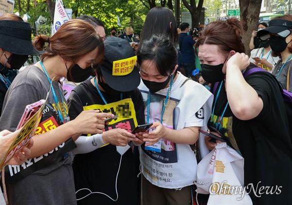 14일 오후 16개월된 입양아 정인이를 학대해 숨지게 한 양부모에 대한 1심 선고가 열리는 서울남부지법앞에서 강력한 처벌을 촉구하는 시위를 벌이던 시민들이 스마트폰으로 재판 속보를 살펴보고 있다.