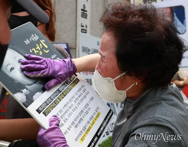 14일 오후 16개월된 입양아 정인이를 학대해 숨지게 한 양부모에 대한 1심 선고가 열린 서울남부지법앞에서 한 시민이 정인이 사진을 어루만지며 눈물을 흘리고 있다.