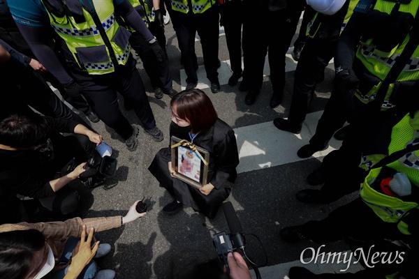 14일 오후 16개월된 입양아 정인이를 학대해 숨지게 한 양부모에 대한 1심 선고가 열린 서울남부지법앞에서 한 시민이 정인이 사진을 들고 주저앉아 강력한 처벌을 촉구하고 있다.