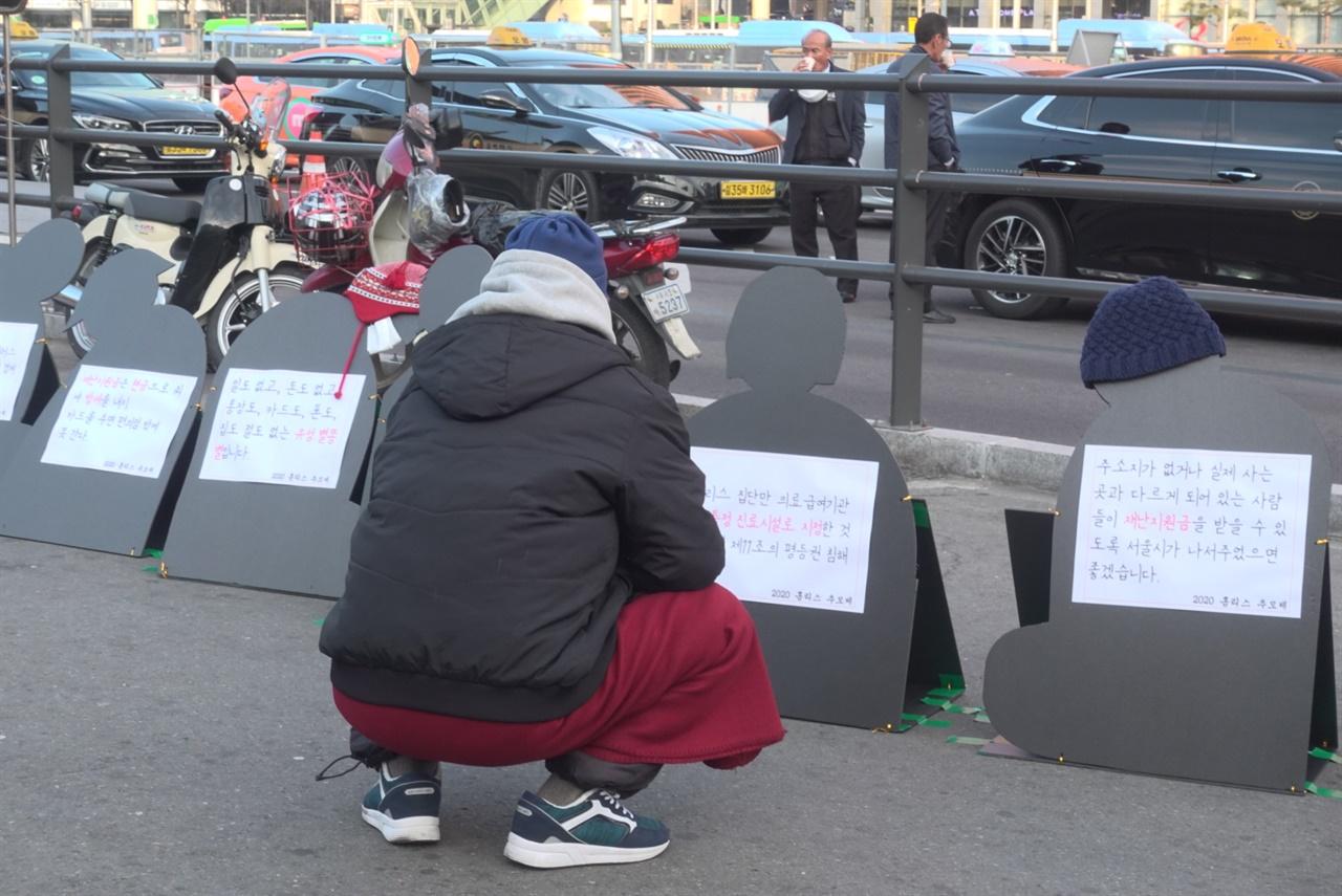 홈리스 추모제 사전 마당 2020년 12월 21일, 동짓날. 이주민 홈리스 L씨가 서울역 광장에 설치된 '홈리스추모제' 선전물을 바라보고 있다.